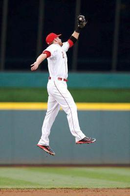 Shortstop getting up high to catch line drive.
